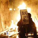 En demonstrant har taget plads på en palle under tirsdagens voldsomme uroligheder i Ferguson. Storjuryens afgørelse, som frikender betjenten, som i sommer skød en ubevæbnet sort teenager, indledte ifølge en anden demonstrant et oprør.