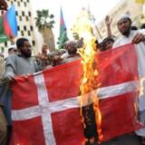 ARKIVFOTO. Pakistanske demonstranter sætter ild til Dannebrog i Karachi i 2008. Kort forinden havde en række danske aviser genoptrykt tegningerne. Foto: AFP / Asif Hassan