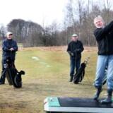 Jens David Jensen gør sig klar til at slå ud i Søllerød Golfklub. De to faste golfmakkere Ary Jeppesen (tv.) og Ernst Møller ser på. I mere end 10 år har de spillet golf året rundt.<br>Foto: Bjarke Ørsted