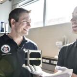 """ARKIVFOTO. Danmarks første ESA-astronaut, den 38-årige Andreas Mogensen, besøgte Aalborg Universitets satellitlaboratorium. Her så han bla.de ingeniørstudendes nye AAUSAT5 satellit som de har lavet til at overvåge skibstrafikken ved Grønland, og han hørte om de andre """"hjemmelavede"""" satellitter er allerede er i kredsløb. Andreas Mogensen skal efter planen sendes op til den internationale rumstation ISS i september i år. Her ser han satellitten som studerende Kasper Hemme holder i hånden."""