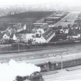 Den Gule By med DSBs centralværksted i baggrunden og et ?damplokomotiv på vej mod Valby i forgrunden set fra en karré ?i Ingerslevsgade omkring 1950. Fra Tine Willer: »Den Gule By«