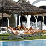 Turister solbader ved poolen på hotel i Tunesien.