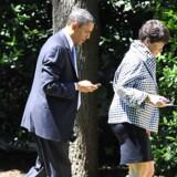 USAs præsident Barack Obama fik kun med besvær lov til at beholde sin Blackberry-telefon, da han tiltrådte embedet. Den blev ekstrasikret og må kun bruges til at kommunikere med en snæver kreds. Her bruger han telefonen, mens han går sammen med sin assistent og rådgiver, Valerie Jarrett. Foto: Ron Sachs, EPA/Scanpix