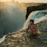 En zambisk mand ser ud over Victoria Falls på Zambezi-floden, som danner grænsen mellem Zambia og Zimbabwe.