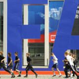 Børn løber forbi et gigantisk logo ved den ligeledes gigantiske forbrugerelektronikmesse IFA (Internationale Funkausstellung) i Berlin. Den varer fra 29. august til 3. september. Foto: John MacDougall, AFP/Scanpix