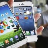 Samsungs Galaxy S4-toptelefon (til venstre) i forhold til Apples iPhone 5. Den kommende topmodel, Galaxy S5, bliver efter sigende endnu større, når den vises frem 24. februar. Arkivfoto: Kim Hong-Ji, Reuters/Scanpix