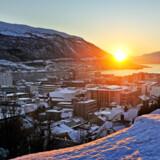 Norske Tromsø 350 km nord for Polarcirklen er blevet Nordens nye klondyke, bl.a. boomer boligpriserne. Der er kraftig vækst i økonomien i Nordens største by i Arktis med 72.000 indbyggere. For flere og flere borgere er det også en livsstil med luksusliv i eksklusive huse, dyre biler og besøg på fancy caféer og restauranter. Mange tromsøværinger, som de lokale beboere kaldes, tjener godt i stillinger i det offentlige eller private erhvervsliv. Billedet af byen er taget onsdag den 21. januar, hvor mørketiden er over og solen første gang efter at have været væk i to måneder og endelig kommer frem over bjerget en kort stund på dagen.