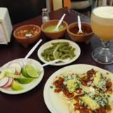 På bordet er der ekstra tilbehør, hvis vi vil have det. To stærke chilisaucer, en grøn og en rød, en tallerken med syltede strimlede kaktus (det er de kendte cowboy-kaktus dog og uden torne, og de smager glimrende) samt en frisk salsa af snittet tomat, løg, koreander og habanero – en ekstra stærk grøn chili.