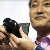 Sony skal fremad og være nyskabende, siger topchefen gennem 18 måneder, Kazuo Hirai, som her viser et af eksemplerne på nyskabelserne: en løs zoomlinse, der kan sættes uden på mobiltelefoner og dermed sikre bedre billeder. Foto: Fabrizio Bensch, Reuters/Scanpix