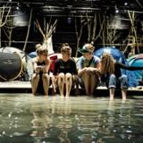 Hele teaterrummet på Republique er forvandlet til en sandstrand med teltlejr og en lille badesø med sommerlunt vand – her er det fra venstre Astrid Haugesen, Sofie Højsted Sørensen, Ludvig Brostrup og Joanna Kastrup, der dypper tæerne.