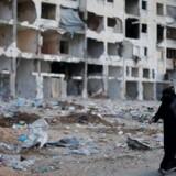 En palæstinensisk kvinde passerer en sønderskudt boligblok i byen Beit Lahiya i det nordlige Gaza.