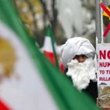 """Mens der forhandles om en aftale om Irans atomprogram i Wien, er der protester på gaden i den østrigske hovedstad. Her en demonstrant med et skilt, hvor der står 'ingen atomvåben til mullaherne"""" i protest mod Irans atomprogram."""