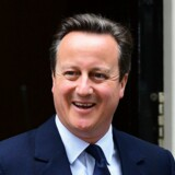 Døren gik op til Downing Street nr. 10, og ud kom premierminister David Cameron – øjensynligt i højt humør inden han mandag i Underhuset skulle give sin udlægning af det britiske nej til EU. Foto: Leon Neal/AFP