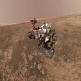 Billedet viser Curiosity i midten af det støvede, røde Mars-terræn med bjerget Sharp i baggrunden.