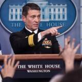 """Præsident Donald Trumps militære livlæge i Det Hvide Hus, admiral Ronny Jackson, trak sig torsdag fra sin nominering til posten som ny minister for veteraner. Han var blandt andet anklaget for at have været fuld på arbejde og strøet om sig med receptpligtig medicin uden at have styr på de fornødne papirarbejde. Her fra januar hvor han efter et helbredstjek af præsidenten sagde, at Trump har """"ufattelig gode gener"""". / AFP PHOTO / NICHOLAS KAMM"""