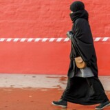 BMINTERN - Muslimsk kvinde i sort tøj ved Den røde plads ved Superkilen på Nørrebro der er blevet malet rød og er afspærret ved træ.