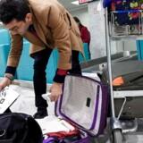Det er farligt at stuve elektronisk udstyr ind i lastrummet i det omfang, som det amerikansk-britiske forbud lægger op til, mener de europæiske flysikkerhedsmyndigheder. Her pakker en rejsende sin bagage om, så den bærbare lægges i kufferten, inden han står på flyvet i den internationale lufthavn i Karthago i Tunesien. Arkivfoto: Fethi Belaid, AFP/Scanpix