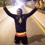 Flere migranter fejrede det, da de nåede over den spanske grænse. REUTERS/Jesus Moron