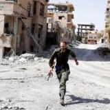En frivillig britisk kriger løber i dækning for mulige snigskytteangreb ved frontlinjen af Raqqa. Foto taget den 7. oktober.
