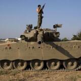 En israelsk soldat tjekker sit våben nær ved grænsen til Gaza søndag morgen, efter det israelske militær har genoptaget kamphandlingerne.