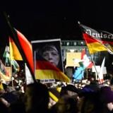 Pegida-sympatisører holder et billede i vejret af kanslor Anglea Merkel iført tørklæde under deres 12. march i Dresden 12. januar. Mandagens demonstration er aflyst