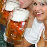 Piger i det traditionelle tøj skåler med ét-liter ølkrus løbet til oktoberfest i München