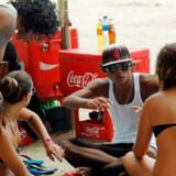 Billedet, taget d. 31. marts 2010, viser to lokale unge mænd der snakker med udenlandske kvindelige turister på Kuta Beach, Bali.