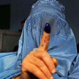 En afghansk kvinde viser sin finger dyppet i blæk efter at have stemt på et valgsted i den nordvestlige del af byen Herat.
