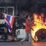 En af de demonstrerende støtter til eks-premierminister Thaksin Shinawatra bærer et thailandsk flag gennem Bangkoks gader, hvor bl.a. busser for tiden sættes i brand.