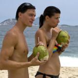 """Et par """"cariocas"""", som indbyggerne i Rio kalder sig, drikker af kokosnødder på Ipanema stranden."""