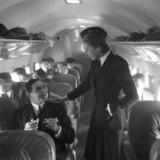 Dengang SAS blev oprettet var det skandinaviske velfærdssystem under oprettelse og drømmene for det fælles nordiske samarbejde var store. Den nuværende krise har truet med at slukke den drøm. På billedet er vi tilbage fra før alting gik af lave, indenfor i et Douglas DC-3 fly, hvor en stewardesse taler med en af de rejsende, der sidder og ryger en cigaret.