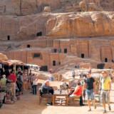 Den smalle Siq med de nærmest skulpturelle former fører ind til Petra, hvor turistboder og småcaféer er rykket ind mellem klippevæggene med de mange gravkamre.