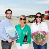 På Marielyst Strand overrækker Rejselivs Mikkel Mayner Lind champagne, blomster og diplom til turistbureauets chef, Majbritt Hammer, og Aida Pedersen fra Sydfalster Turist- og Erhvervsforening.