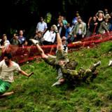 Osterulning i Coopers Hill i Brockworth, Gloucestershirede. Deltagerne kaster sig selv ned af den store bakke med morsomme resultater.
