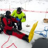 Hovedet over isen, resten under. Det er vigtigt ikke at gå i panik, for hullet, man kan søge hen til og komme op i den livgivende luft, er ikke ret stort.
