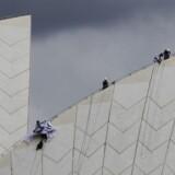 Torsdag morgen kravlede flere aktivister op på toppen af Operahuset i Sydney for at vise deres vrede over Australiens flygtningepolitik. Det er ikke første gang, Sydney Opera House lægger mursten til protester. Her på billedet ses aktivister fra Greenpeace i 2009. Reuters/Daniel Munoz/arkiv