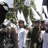 Arkivfoto: En indonesisk politimand og medlemer af Hizb ut-Tahrir.