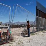 En dreng kigger på amerikanske arbejdere, som bygger på en del af muren i Sunland Park i USA over for grænsebyen Ciudad Juarez. September 2016.