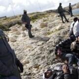 Arkivfoto: Tunesiske flygtninge bliver overvåget af det italienske bagmandspoliti »Guardia di Finanza« på Lampedusa 31. marts, 2011. REUTERS/Tony Gentile