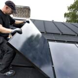 Hvilke energikilder er bedst, når der skal varmes op i hjemmet? Berlingske har undersøgt sagen - her ses solceller blive installeret på taget af et privat hjem.