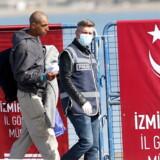 En mand ekstores af tyrkisk politi som en af de første af morgenens deporterede flygtninge og migranter fra Grækenland.