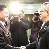 Den sydkoreanske diplomat Lee Woo-sung (til højre) giver hånd til den nordkoreanske diplomat Kwon Hook-bong (til venstre) d. 15. januar. De to har diskuteret en eventuel nordkoreansk deltagelse i OL i Sydkorea.