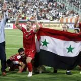 Det syriske fodboldlandshold fejrer, at de nu har en billet til VM i Rusland efter 2-2 mod Iran på Azadi stadion i Teheran den 5. september. / AFP PHOTO / ATTA KENARE
