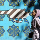 TOPSHOTS An Iranian woman walks past a mural showing a gun painted with an interpretation of the American flag on the wall of the former US embassy in Tehran on September 25, 2013. Leaders from Iran and the United States have not met since the 1979 Islamic Revolution brought often open hostility to their contacts, particularly over Iran's contested nuclear program. AFP PHOTO/ATTA KENARE