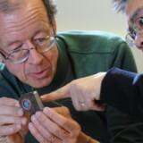 Forskerne Arto Nurmikko (tv.) og Ming Yin undersøger en prototype på en enhed, der kan registrere signaler fra hjernen og overføre dem trådløst. Foto: Fred Field, Brown University