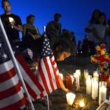 Der tændes lys for de tolv ofre og 51 sårede efter den 247-åriges besærkergang i Denver-biograf.