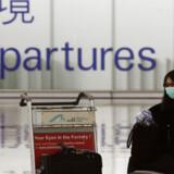 En passager bærer maske i afgangshallen i lufthavnen i Hong Kong, som onsdag kunne bekræfte den anden smittede med svineinfluenza i landet.
