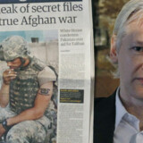 WikiLeaks-grundlægger Julian Assange, her med en af avisforsiderne om de de første afsløringer fra Afghanistan, bliver undersøgt for upassende optræden overfor en kvinde i Sverige.