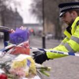 En politibetjent lægger blomster ved Westminster dagen efter terrorangrebet, der ramte det centrale London.