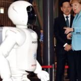 Bilproducenten Honda indstiller videreudviklingen af kändisrobotten Asimo. Robotten Asimo tager en lille svingom med den tyske forbundskansler Angela Merkel under sidstnævntes besøg på en messe i Tokyo i 2015. Bagest ser den tidligere astronaut Mamoru Mori til. Arkivfoto: Yoshikazu Tsuno, AFP/Scanpix